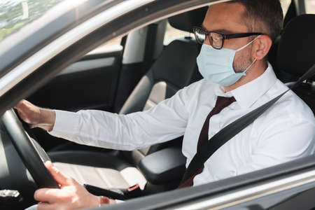 Selective focus of businessman in medical mask driving car