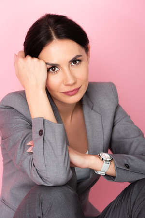 beautiful businesswoman in suit looking at camera isolated on pink