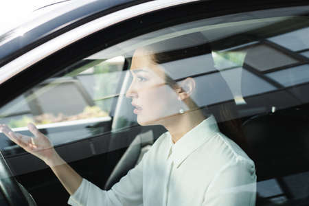 Selective focus of confused businesswoman pointing with hand while driving car
