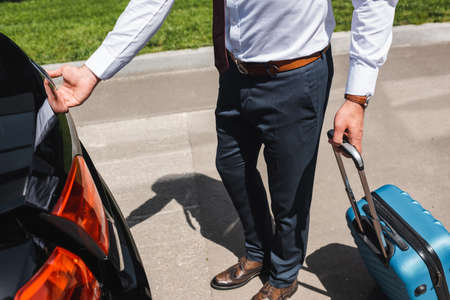 Cropped view of businessman holding suitcase and opening car trunk on urban street Reklamní fotografie