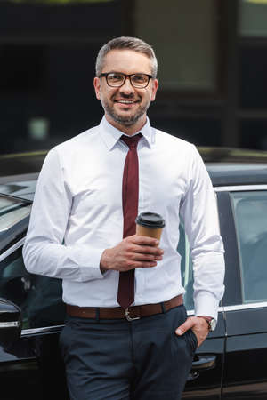 Handsome businessman holding coffee to go near car and smiling at camera on urban street
