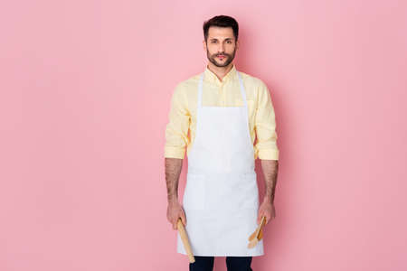 handsome bearded man holding rolling pin and wooden spoon on pink