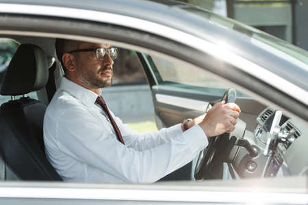Side view of handsome businessman driving car