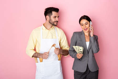 handsome man in apron holding wooden spoons and looking at businesswoman with money talking on smartphone on pink