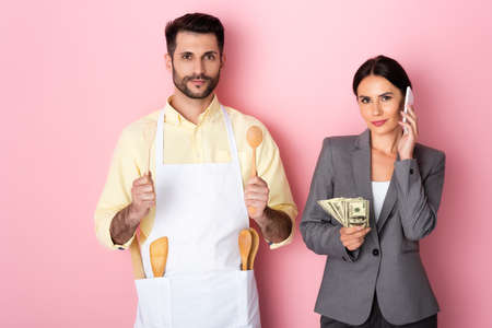 handsome man in apron holding wooden spoon and spatula near businesswoman with money talking on smartphone on pink