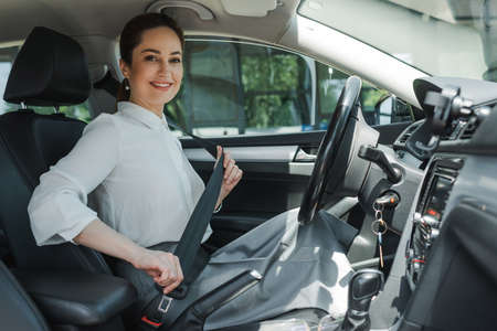 Beautiful businesswoman smiling at camera while holding seat belt in auto
