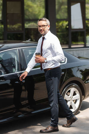Smiling businessman looking at camera while holding paper cup near auto on urban street
