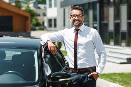 Selective focus of businessman with hand in pocket smiling at camera near car on urban street Reklamní fotografie
