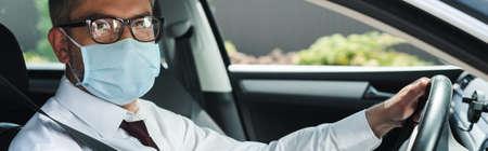 Panoramic shot of businessman in medical mask looking at camera while driving car Reklamní fotografie