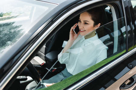 Smiling businesswoman talking on smartphone while sitting on driver seat in car