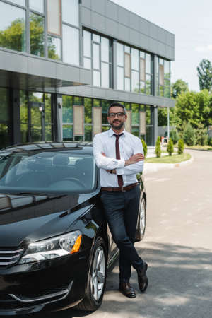 Handsome businessman with crossed arms looking at camera near car on urban street Reklamní fotografie