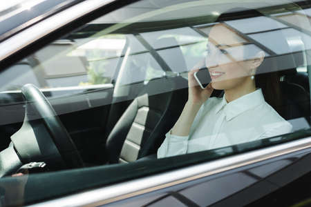Selective focus of businesswoman smiling while talking on smartphone on driver seat in car