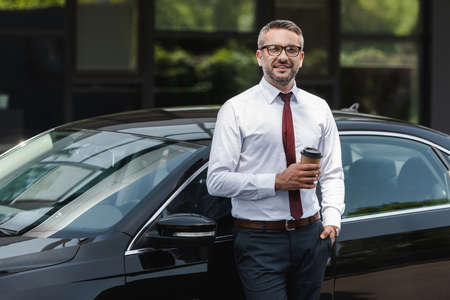 Handsome businessman smiling at camera and holding coffee to go near auto on urban street