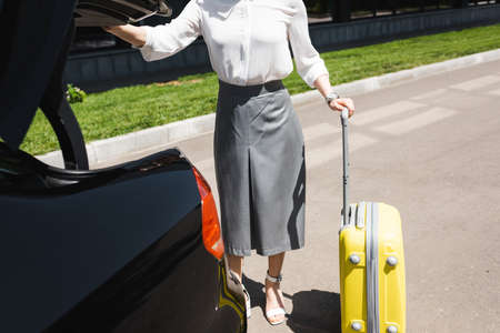 Cropped view of businesswoman opening car trunk near suitcase on urban street