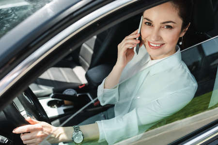 Selective focus of businesswoman smiling at camera and talking on smartphone on driver seat in auto Reklamní fotografie