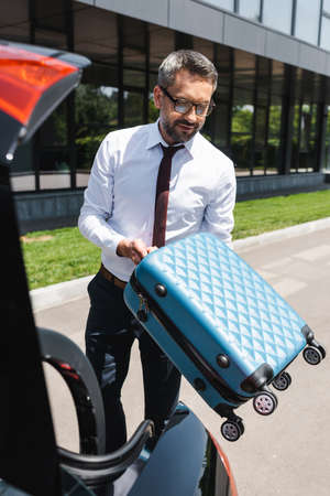 Selective focus of handsome businessman holding suitcase near car with open trunk on urban street