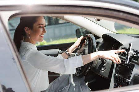Side view of smiling businesswoman using smartphone while driving auto