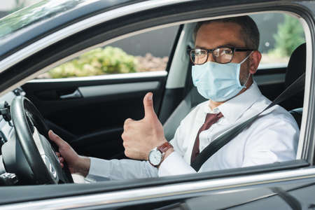 Selective focus of businessman in medical mask showing thumb up while driving auto Reklamní fotografie