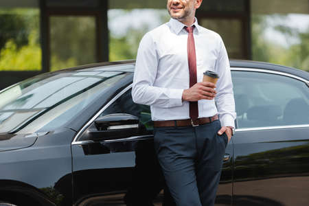 Cropped view of smiling businessman holding paper cup near auto on urban street