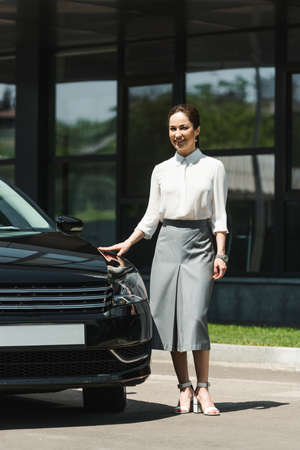 Attractive businesswoman smiling at camera while standing near car on urban street Reklamní fotografie