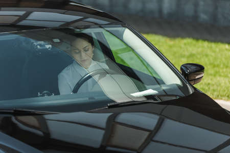 Beautiful businesswoman sitting on driver seat in car
