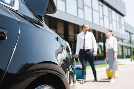Selective focus of business couple walking with luggage to car on urban street