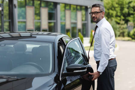 Side view of handsome confident businessman standing near car with open door on urban street