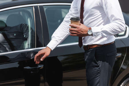 Cropped view of businessman holding coffee to go and opening car door on urban street
