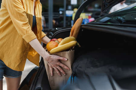 Cropped view of woman putting shopping bag with food in car trunk on urban street Foto de archivo