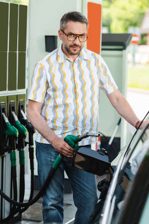 Selective focus of handsome man looking at camera while holding fueling nozzle near car on car refueling station Foto de archivo