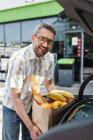Selective focus of smiling man putting shopping bag with food in open car trunk on urban street Foto de archivo