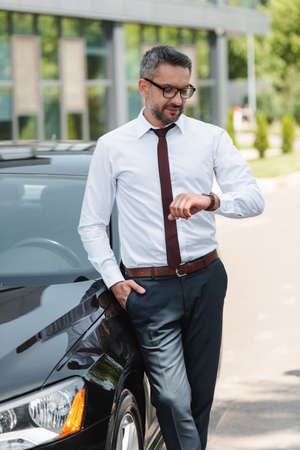 Handsome businessman looking at wristwatch near car on urban street