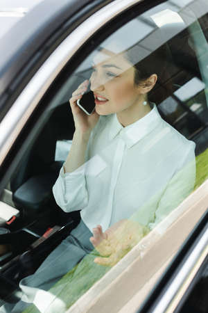 Selective focus of businesswoman talking on smartphone in car Foto de archivo