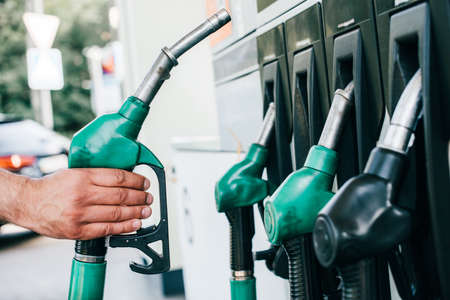Cropped view of man holding fueling nozzle on gas station on urban street Banco de Imagens