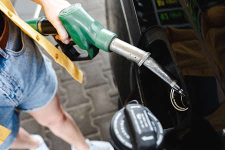 Cropped view of woman holding fueling nozzle near car on gas station Reklamní fotografie