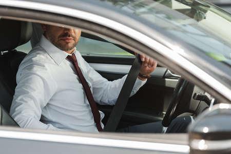Selective focus of businessman holding seat belt in car Archivio Fotografico