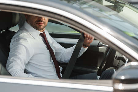 Selective focus of businessman holding seat belt in car Banco de Imagens