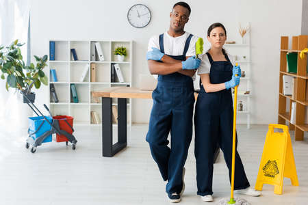 Multicultural cleaners with mop and brush looking at camera near wet floor sign in office