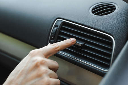 Cropped view of woman adjusting air conditioner in car