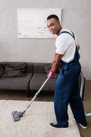 African american cleaner in uniform cleaning carpet and looking at camera in living room