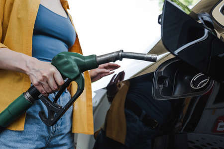 Cropped view of woman holding fueling nozzle near auto on gas station