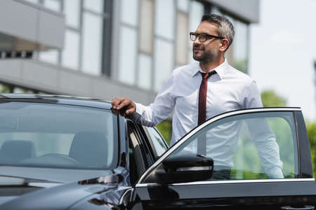 Selective focus of handsome businessman standing near car with open door on urban street