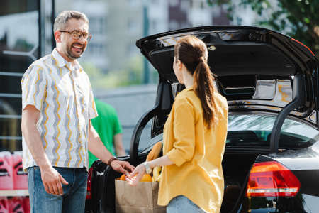 Selective focus of smiling man looking at woman near open car trunk on urban street