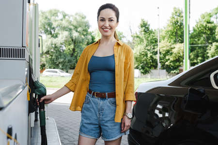 Selective focus of beautiful smiling woman holding fueling nozzle near car on gas station