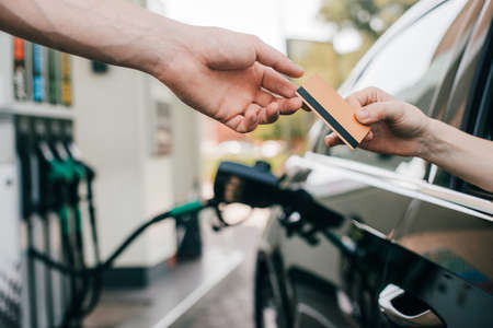 Cropped view of woman giving credit card to worker of gas station while fueling auto
