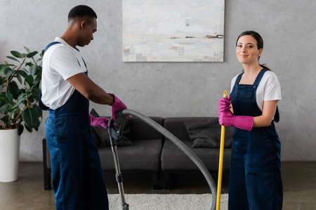 Smiling cleaner in uniform looking at camera near african american colleague with vacuum cleaner Imagens