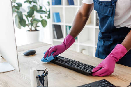 Cropped view of african american cleaner in rubber gloves cleaning computer keyboard on office table