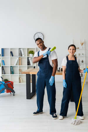 Positive multiethnic cleaners with brush and mop looking at camera in office