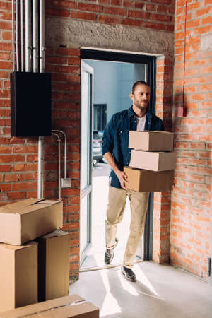 handsome businessman holding carton boxes while moving in new office Reklamní fotografie