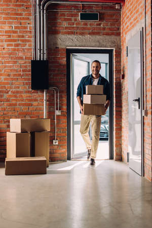happy businessman holding carton boxes while moving in new office Reklamní fotografie